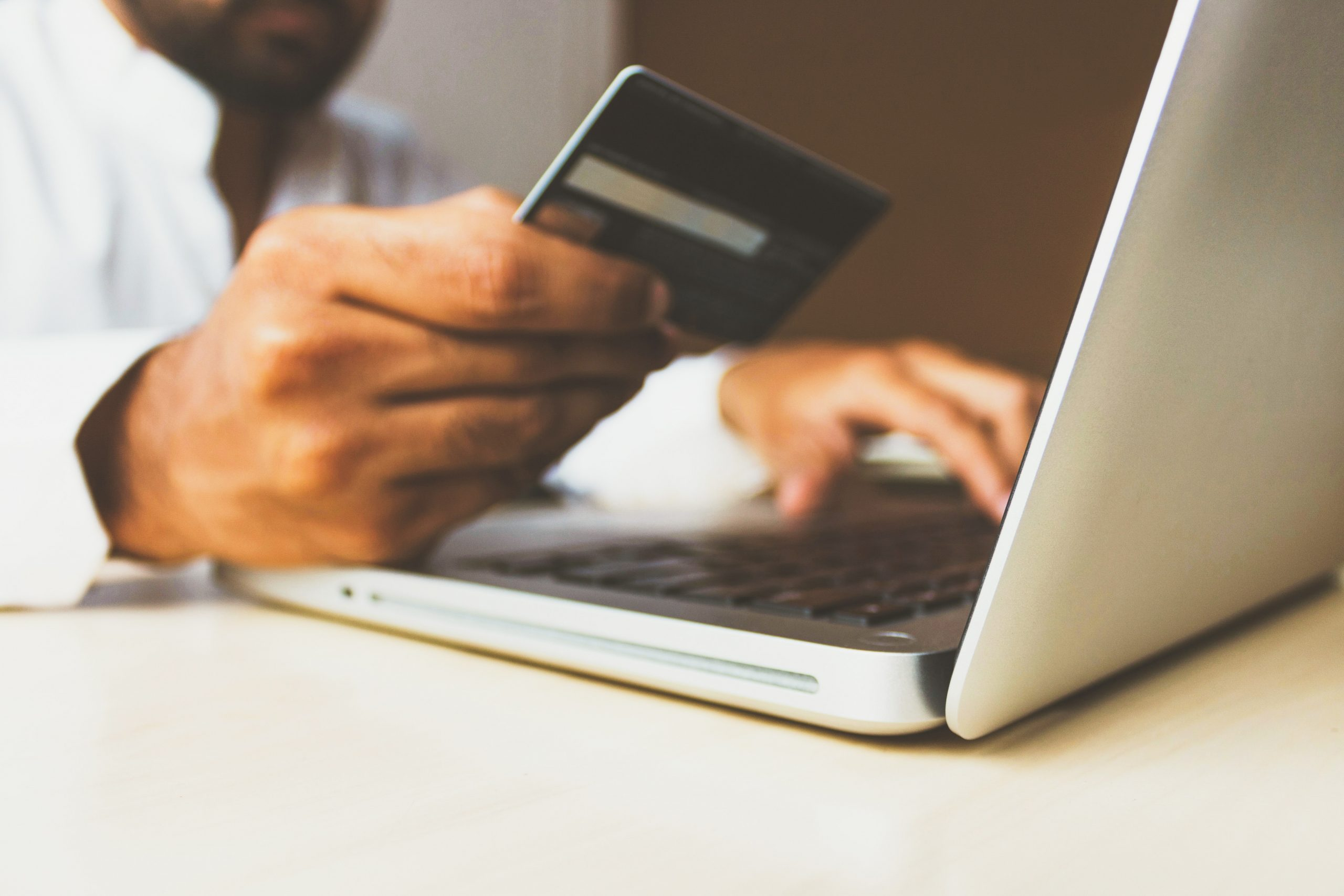 person using laptop computer holding a debit card